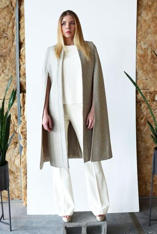 The Obi Cape is made of a beautiful sand melange melton wool and boasts of a clean tailored look. The cape has long openings for the arms and hangs beautifully.